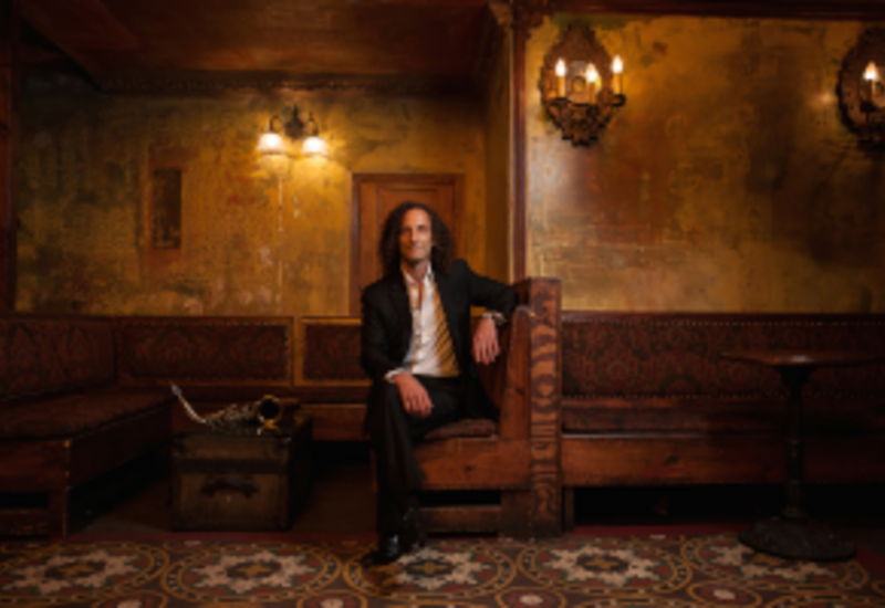 Kenny G sitting on a sofa