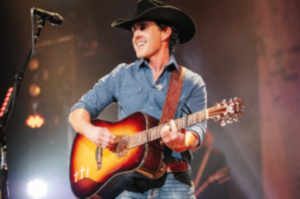 Aaron Watson with guitar on stage